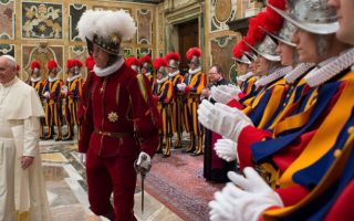 In this photo taken Monday, May 5, 2014, and provided by the Vatican newspaper L'Osservatore Romano, Pope Francis, flanked by Swiss Guards Commander Daniel Rudolf Anrig, greets new Swiss Guards the day before their swearing-in ceremony, as he arrives to meet them in the Clementine hall at the Vatican.  (AP Photo/L'Osservatore Romano)/OSS101/374662201042/PHOTO TAKEN MONDAY, MAY 5, 2014 AP PROVIDES ACCESS TO THIS PUBLICLY DISTRIBUTED HANDOUT PHOTO PROVIDED BY THE VATICAN NEWSPAPER L'OSSERVATORE ROMANO /1405061610
