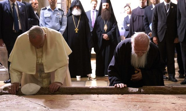 Pope Francis and Constantinople Patriarch Bartholomew kneel to kiss the Stone of Unction, traditionally claimed as the stone where Jesus' body was prepared for burial, in the Church of the Holy Sepulchre, in Jerusalem, Israel, Sunday, May 25, 2014. The two spiritual leaders prayed for unity at the Church of the Holy Sepulcher, the site where Christians believe Jesus was crucified, buried and resurrected. (AP Photo/Andrew Medichini, Pool)/AJM140/324809711315/POOL PHOTO/1405252131