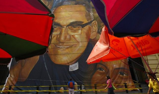 A man observes a giant banner with the picture of Archbishop Oscar Romero in San Salvador, on March 22, 2015. The Catholic community expects the beatification of Archbishop Romero on May 23, 2015 in San Salvador. AFP PHOTO / Marvin RECINOS